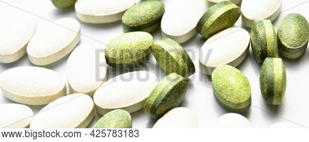 White And Green Oval Tablet Pills Isolated On White Background, Medical Oval Pills Tablets