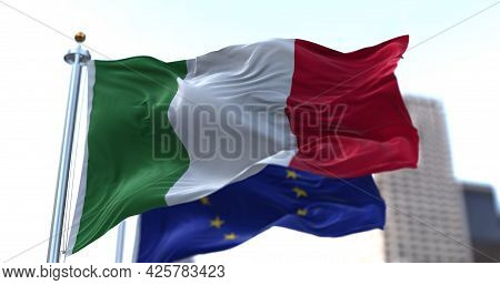 The National Flag Of Italy Waving In The Wind Together With The European Union Flag Blurred In The B