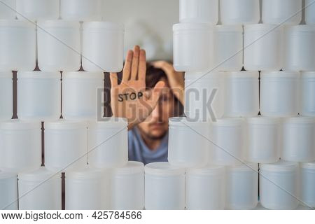 Man Showing Stop Surrounded By Many Jars Of Yoghurt That He Uses In A Year. A Huge Amount Of Plastic
