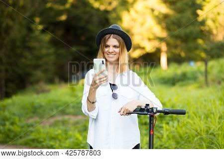 Outdoor Portrait Of Young Beautiful Girl In Black Hat Standing With Her Electric Scooter While Typin