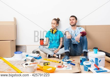 Happy Couple Together Sitting On Floor Among Cardboard Boxes. Young Man And Woman Relaxing After Mov