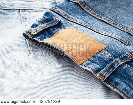 Blue Jeans With A Brown Leather Blank Label, Close-up. Jeans Texture. Fashion Denim Background For S