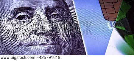 Benjamin Franklins Face On A Hundred-dollar Bill Next To A Credit Card. Close-up. A Hundred-dollar A