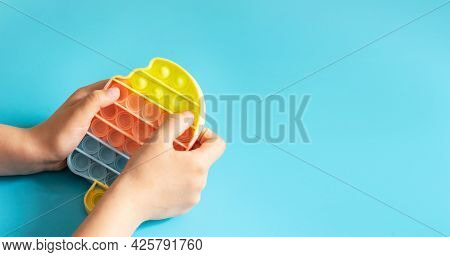 Fashionable Touch Bright Toy Antistress Pop It In Childrens Hands Blue Background Copy Space