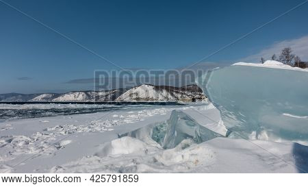 Snowdrifts And Blocks Of Ice Lie On The Bank Of The Non-freezing River. Turquoise Shiny Hummocks Wit