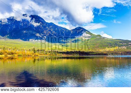 Mount Pyramid is covered by cumulus clouds. Pyramid Lake. Picturesque small island overgrown with pine and fir trees. Cold sunny day in the Rocky Mountains of Canada.