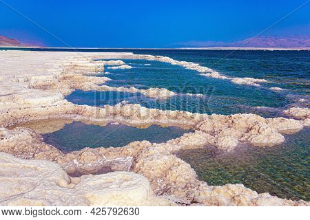The Israeli coast of the Dead Sea. Windy spring day. The evaporated salt protrudes above the water.