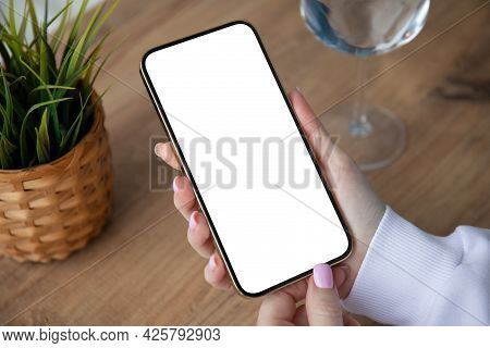 Female Hands Holding Phone With Isolated Screen On Background Of Table In Cafe