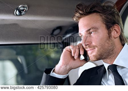Businessman in full suit traveling in luxury limousine. Sitting in car calling on phone. Business travel concept.