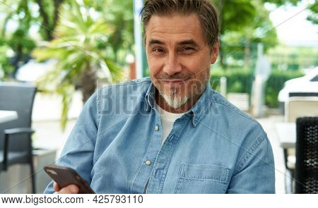 Outdoor portrait of mid adult man in 50s, happy confident smile using phone. Mature age, middle age, bearded.