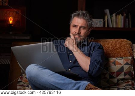 Man sitting on couch at home with laptop computer. Businessman working in home office. Portrait of mature age, middle age, mid adult man, bearded, thinking, authentic look.