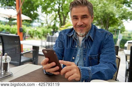 Outdoor portrait of mid adult man in 50s, happy confident smile using phone. Sitting on restaurant terrace. Mature age, middle age, bearded.