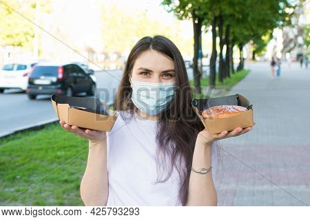 A Masked Woman Deliverer Of Food During A Pandemic And Quarantine Keeps Food To Order In Cardboard B