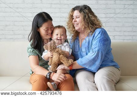 Happy Diverse Lesbian Couple Sitting On Sofa At Home And Playing With Child