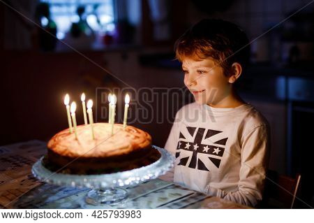 Adorable Happy Blond Little Kid Boy Celebrating His Birthday. Child Blowing Seven Candles On Homemad