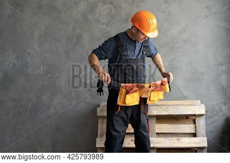 A Male Builder Or Repairman Puts On A Tool Belt. The Constructor Stands Against A Gray Wall Wearing