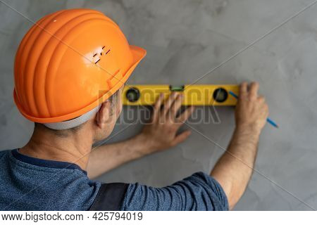 Close-up Architect Or Construction Worker In Hardhat Checking Level Of The Wall With The Level Tool.