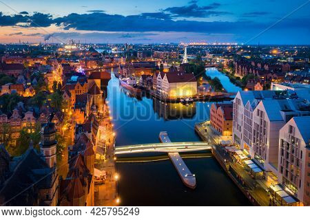 Amazing architecture of the main city in Gdansk at dusk, Poland. Aerial view of the historical Port Crane at the Motlawa river