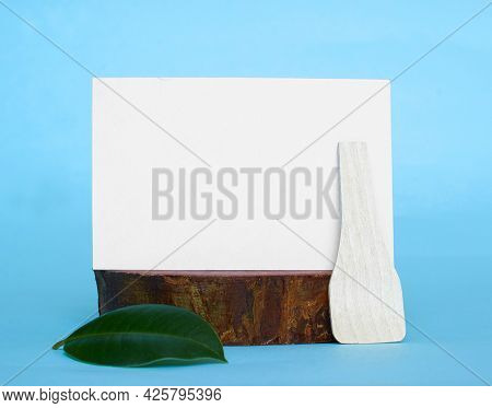 A White Cardboard Card With A Place For Text, A Green Ficus Leaf And A Wooden Spoon On A Wooden Stan