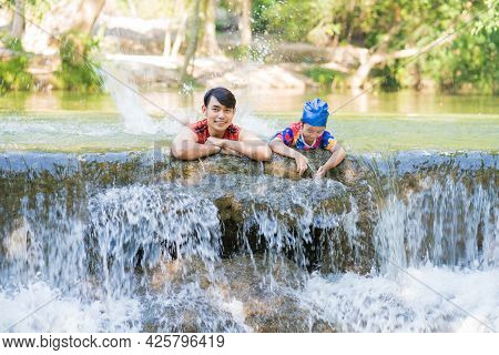 Happy Father With Daughter Enjoy The Waterfall. Traveling Nature Near A Beautiful Waterfall At Chet