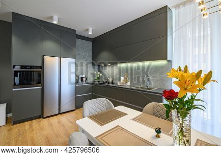 Modern trendy luxury dark gray kitchen with dining table