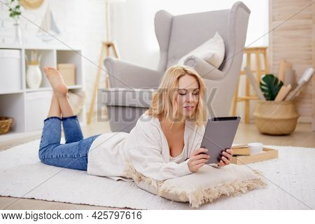 Young Beautiful Woman Lying On The Floor And Using Tablet Pc In Bright Living Room