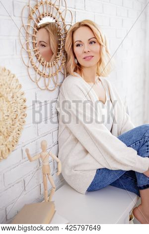 Home And Cosiness Concept - Portrait Of Young Beautiful Slim Woman Sitting On Shelf At Home