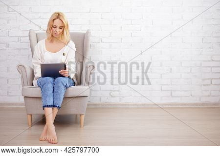 Young Beautiful Woman Sitting In Armchair And Using Tablet Pc - Copy Space Over White Brick Wall Bac