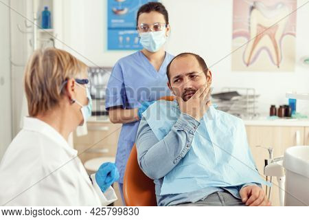 Sick Man Having Symptoms Of Tooth Pain Holding Hand On Cheek While Talking With Senior Doctor. Patie