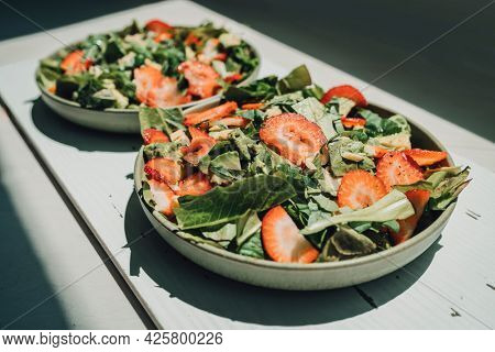 Healthy food at home. Fresh salads lunch meal two plates of kale lettuce and strawberries.
