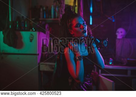 Girl In A Futuristic Cyberpunk Costume With Neon Lighting. The Concept Of The Future Post-apocalypse