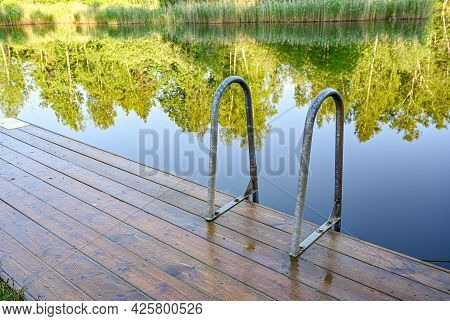 Wooden Jetty With Bathing Ladder In Early Morning