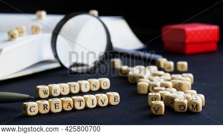 Creative Writing Lettering Next To Open Textbook, Magnifying Glass, Pen And Red Gift Box. Concept Of