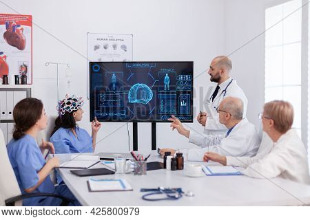 Neurologist Man Doctor Checking Brain Expertise Using Headset With Sensors On Woman Asisstant In Hos