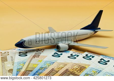 Commercial Airplane Toy And A Pile Of Euro Banknotes. Flights Cost Concept