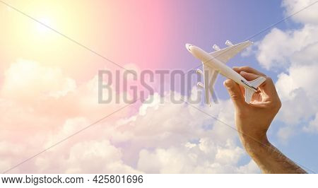 Flying Plane On The Blue Sky Banner Background. A Toy Plane In Hand Flies To Travel. Summer, Vacatio