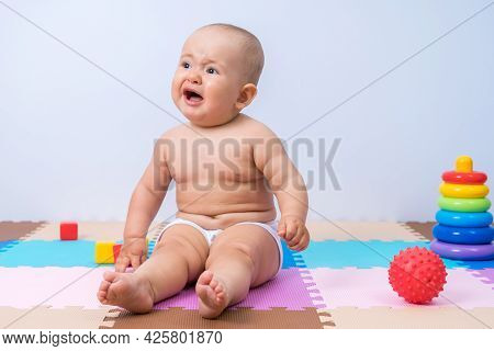 Newborn Baby Crying While Sitting On The Floor In The Playroom