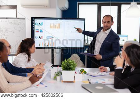 Manager Holding Briefing Presentation In Conference Room Monitor Project. Corporate Staff Discussing