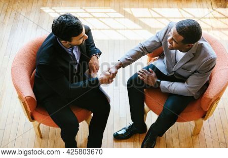 Business people greeting by shaking their hands