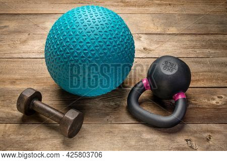 heavy rubber slam ball filled with sand, small iron kettlebell and a dumbbell on a rustic wood background,  training, exercise and fitness concept