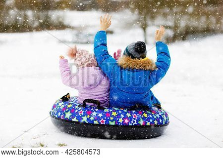 Active Toddler Girl And School Boy Sliding Together Down The Hill On Snow Tube. Children, Siblings H