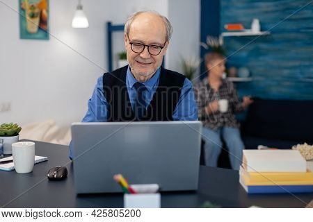 Old Woman Relaxing On Couch Holding A Cup Of Coffee And Husband Is Working. Elderly Man Entrepreneur