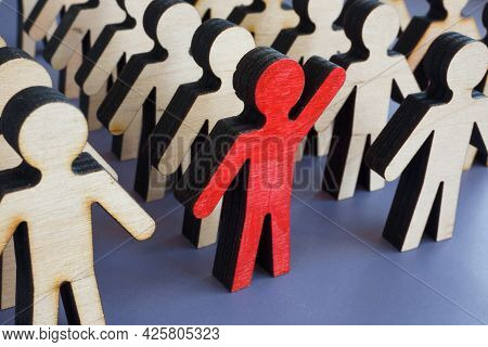 Initiative And Activism Concept. Unique Figurine With A Raised Hand In A Crowd.