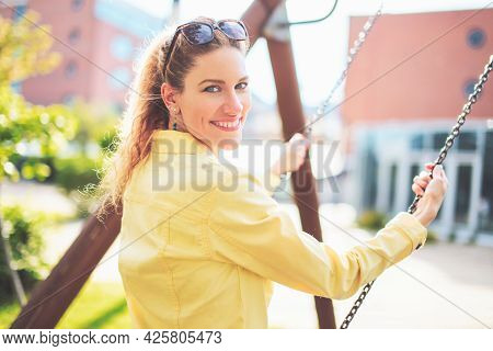 Happy Young Positive Caucasian Woman Swinging In Park And Looking Back