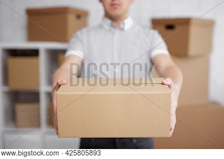 Postal Delivery Concept - Close Up Of Man Giving A Box In Warehouse Or Post Office