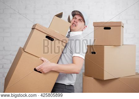 Moving Day Or Delivery Concept - Tired Deliveryman Holding Many Boxes In Hands