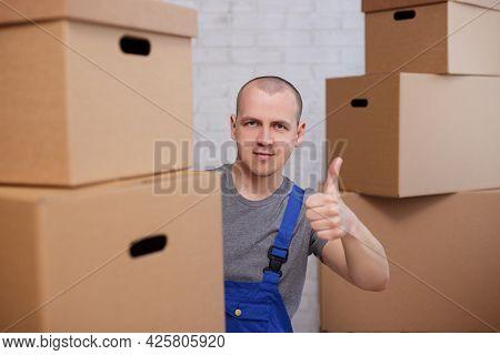Happy Loader Man Thumbs Up Between Cardboard Boxes