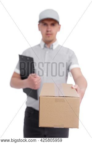 Portrait Of Postman In Uniform Giving A Box Isolated On White Background - Focus On Cardboard Box