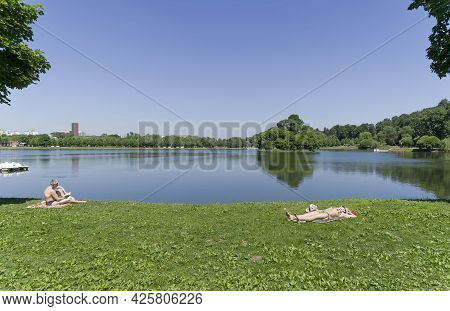 Moscow, Russia - June 20, 2021: People Are Sunbathing On The Bank Of The Upper Tsaritsyn Pond. Tsari