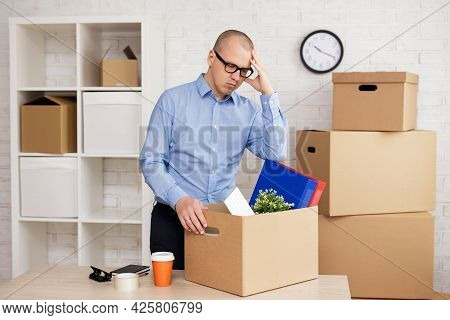Dismission And Moving Day Concept - Sad Businessman Packing Things In Boxes For Moving